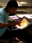 Boy drawing sunset over Angkor